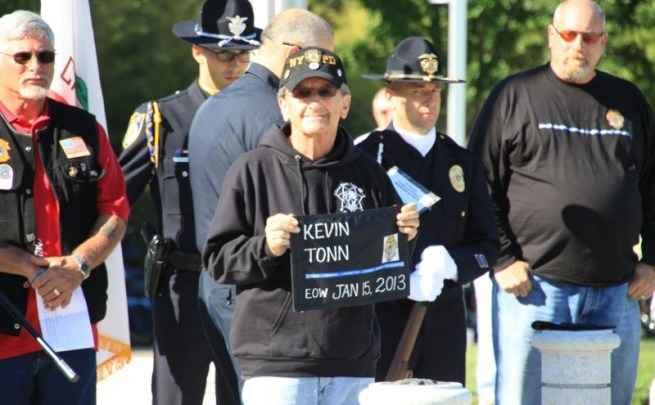 Ed Tonn, Kevin's uncle, holds a plaque during the ceremony showing Kevin's End of Watch date