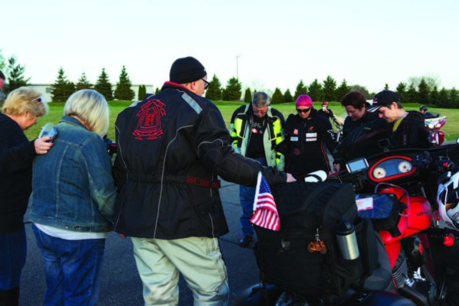 Family and friends gathered around to bless Faith and her bike for the journey ahead
