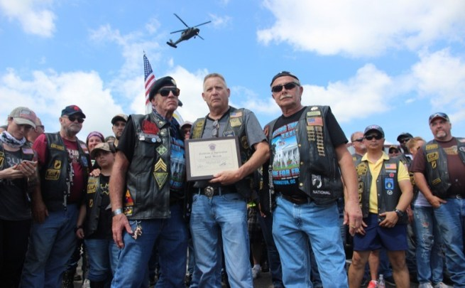 """Andrew """"Devildoc"""" Mutchler, president of Hogs and Heroes, presents a plaque to Artie Muller, Director of Rolling Thunder"""