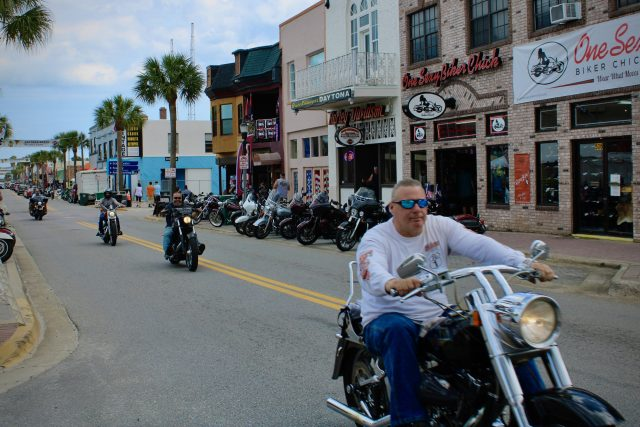 Bikers on v-twin motorcycles cruise Main Street at Daytona Beach Bike Week 2020.