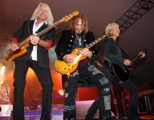 REO Speedwagon's guitar guys, Bruce Hall, Kevin Cronin, and Dave Amato posed for the cameras and a packed house during their Friday night concert on the big stage at Arizona Bike Week
