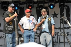 Ray Manzo (r), Rolling Thunder founder, addresses the crowd prior to the unveiling of the tribute bikes on the main stage