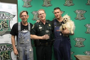 Bill (l), Josh (r) and Cutie Pie present Volusia County Sheriff Ben Johnson with their own special brand of moonshine