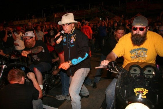 Jay Allen cheers contestants Bill Dodge and Joe Mielke on as they ready for the burnout contest in downtown Sturgis.