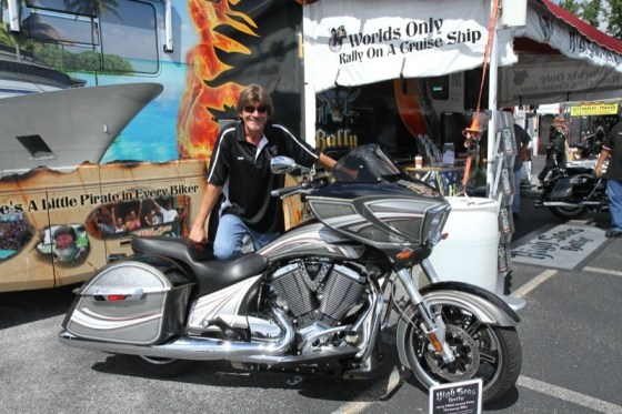 Dean Anderson displays the 2013 Victory Cross Country that will be given away on the High Seas Rally cruise this year