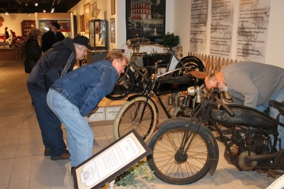 Rich Adams and Ron Lemendola talk old bikes with curator Bruce Williams (r)