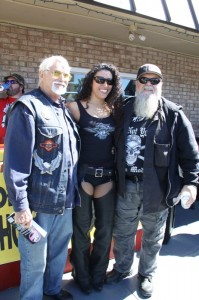 "W.T. ""Roadblock"" Harrell (l) and Willie Jones pose with a Tropical Tattoo hottie outside of the shop"