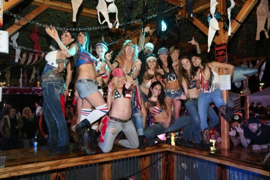 The Hogs & Heifers girls gather for a friendly greeting on their huge traveling bar