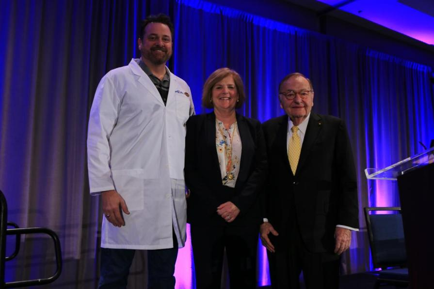Harley-Davidson Director of Government Affairs Ed Moreland trades in his leather jacket for a symbolic white lab coat, a special award to recognize Harley-Davidson's fundraising efforts for the Muscular Dystrophy Association's research program. The Harley-Davidson family has raised more than $103 million over 38 years to advance treatments and cures for neuromuscular diseases. MDA President and CEO Lynn Vos and MDA Chairman of the Board R. Rodney Howell, M.D., presented the award.