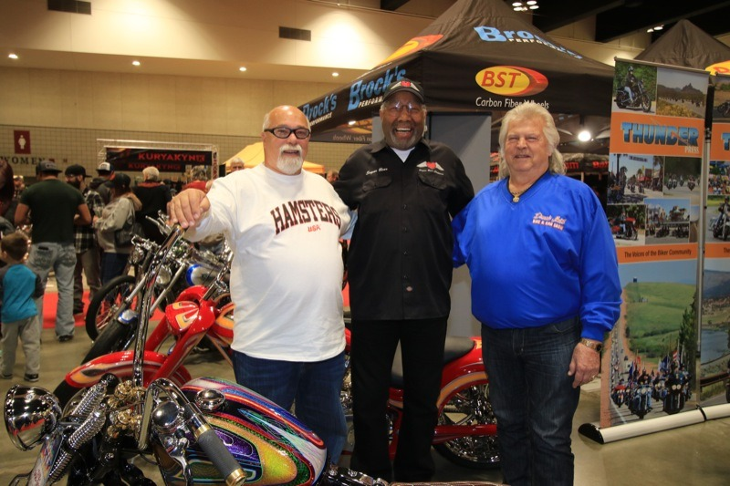 (L.–r.) Dave Perewitz and Sugar Bear check out one of Donnie Smith's creations