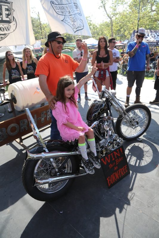 Paul Kuvelis, the winner of the a Prism-built Shovelhead Chopper, poses for some pictures with his new best friend, a little girl who was chosen from the crowd to draw the winning ticket