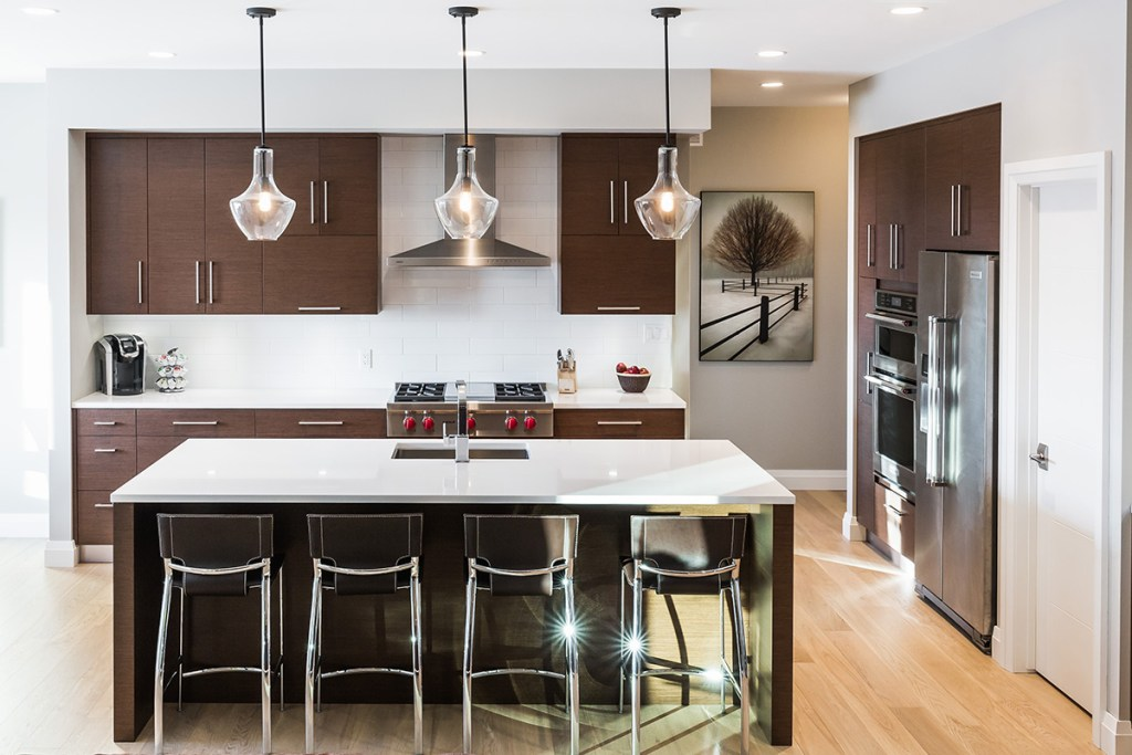 Dark Brown Contemporary Kitchen with white Quartz countertops. Island with overhand and barstools. Stainless Steel appliances and modern light fixutres