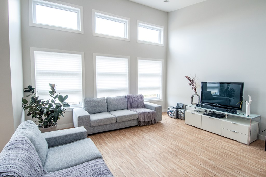 Spacious Living room featuring large windows, laminate flooring, grey couches and contemporary TV stand
