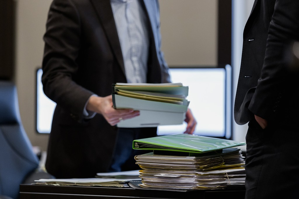 GTP Chartered Professional Accountants - stack of paperwork on desk. Accountants seen standing together holding paperwork