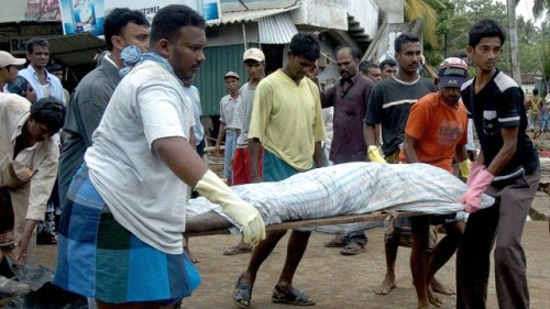 ri Lankan health officials and relatives carry the body of a dead man away in Galle on December 27, 2004.