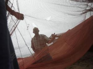 Fishermen inspect their fishing net on the beach in Seenigama