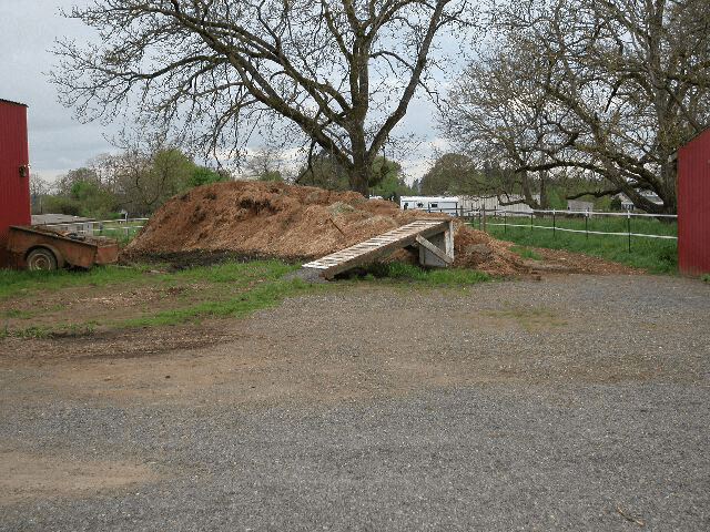 (Photo 8) Manure is piled, uncovered, more than 100 feet from a stream or other waterbody and is more than 250 feet away from a drinking water source. Livestock holding areas are more than 100 feet from surface water bodies and drinking water sources.