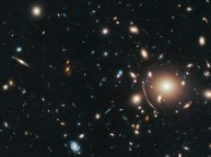 Galaxy Cluster Abell 383 - So much stuff that the light from the galaxies in the back is pulled up front and stretched in to wide arcs. This is called gravitational lensing.