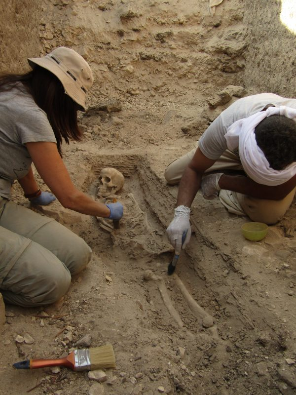 Victoria Peña, arqueoantropóloga del Equipo 2020 del templo de Tutmosis III limpiando esqueleto hallado en tumba junto a un obrero