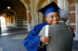 Smiling Black woman holding graduation diploma and hugging husband