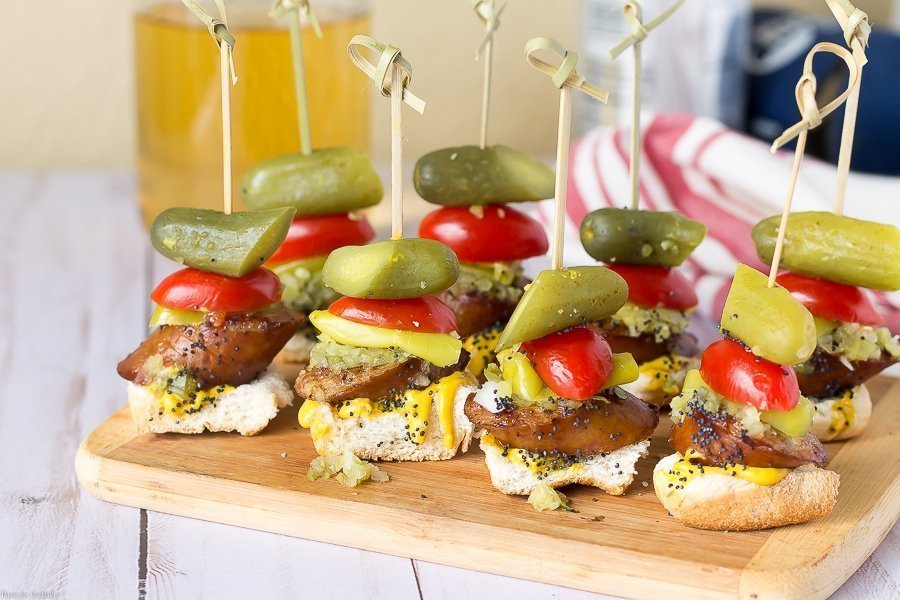 toasted bun, thick slice of smoked sausage, sweet relish, white onion, yellow mustard, pickle spear, sesame seeds, all in one bite on a skewer