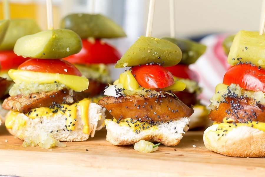 toasted bun, thick slice of smoked sausage, sweet relish, white onion, yellow mustard, pickle spear, sesame seeds, all in one bite on a skewer, horizontal closeup