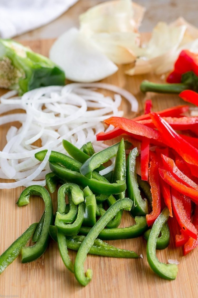 Sliced white onion, green and red bell peppers for 15-Minute Chicken Fajita Cauliflower Rice Bowls