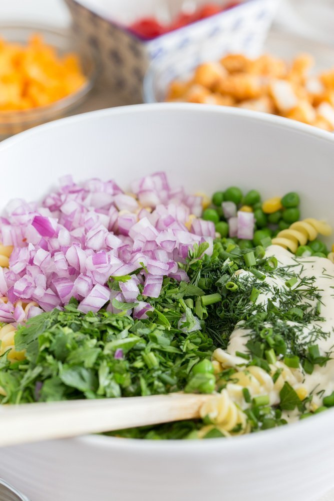 bowl of cooked rotini pasta with diced red onions, chopped chives, parsley, dill, and creamy garlic dressing for Loaded Fried Chicken Pasta Salad