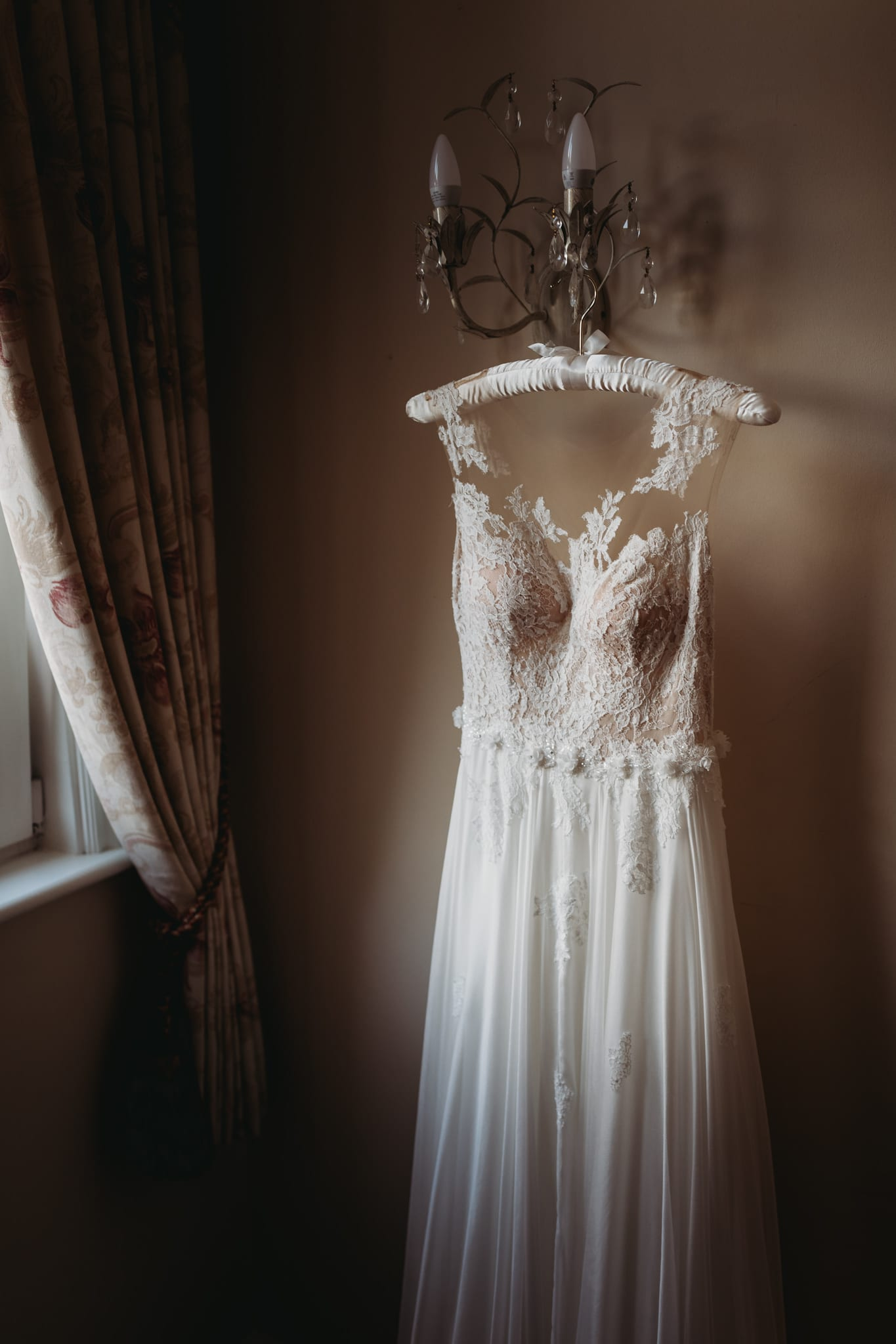 closeup of wedding dress hanging from a chandelier