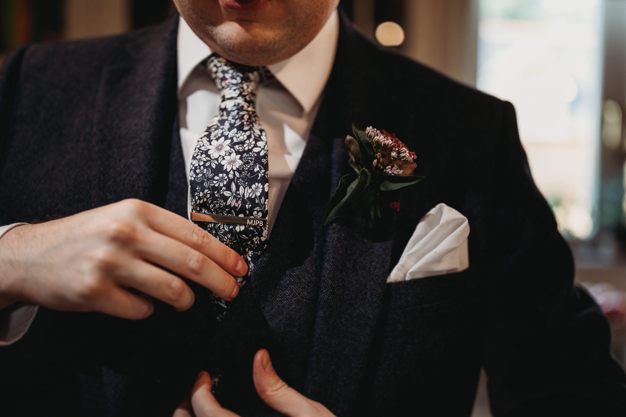 closeup of suit, tie, buttoniere details