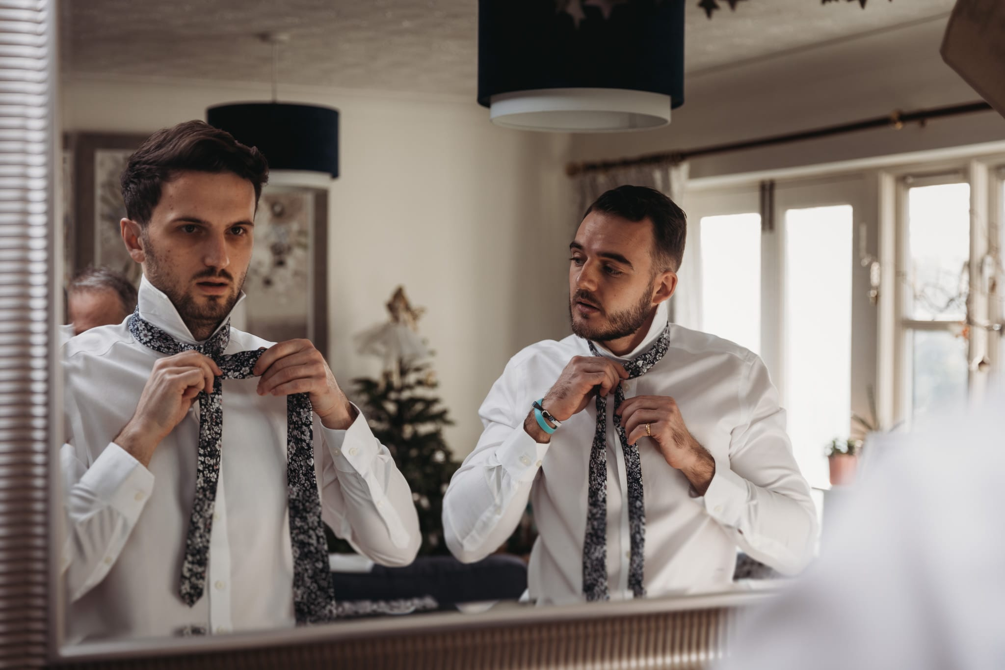 groom and best man trying to tie their ties