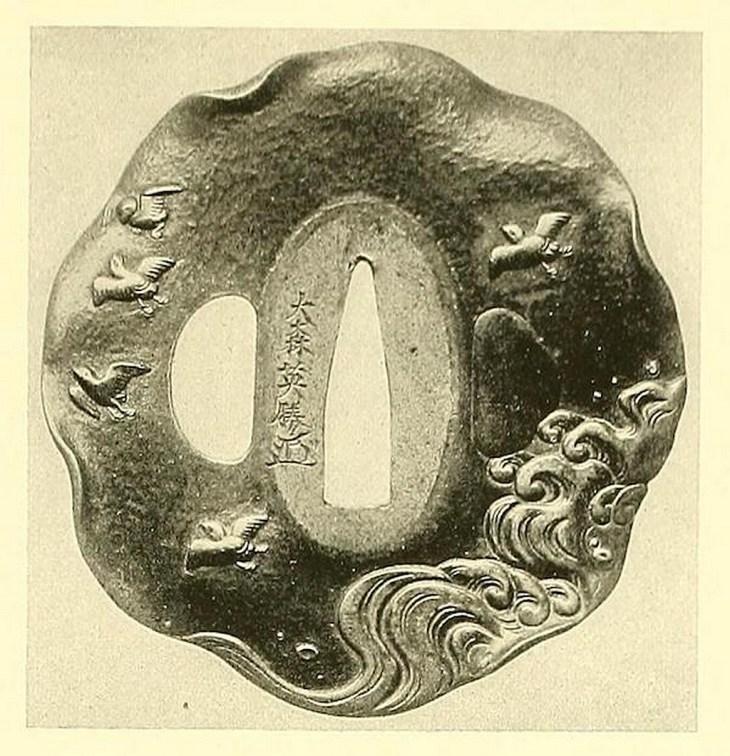Tsuba en bronze jaune. En relief et incrustés d'or, d'argent et de shibuichi, des pluviers (chidori) au-dessus des vagues