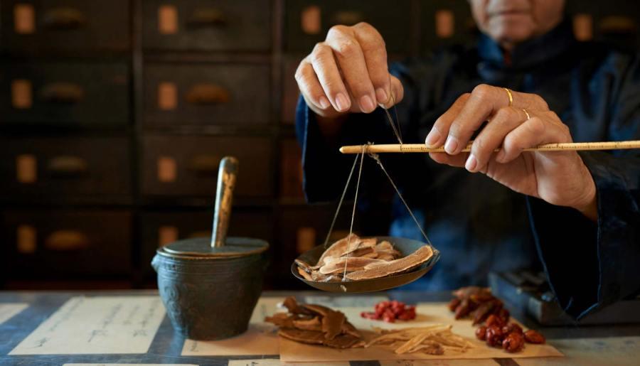 Un homme mesurant les ingrédients chez un apothicaire asiatique traditionnel