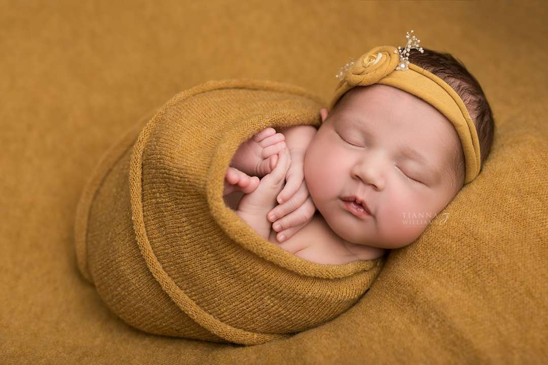 Newborn Baby Wrapped in Mustard - Close Up