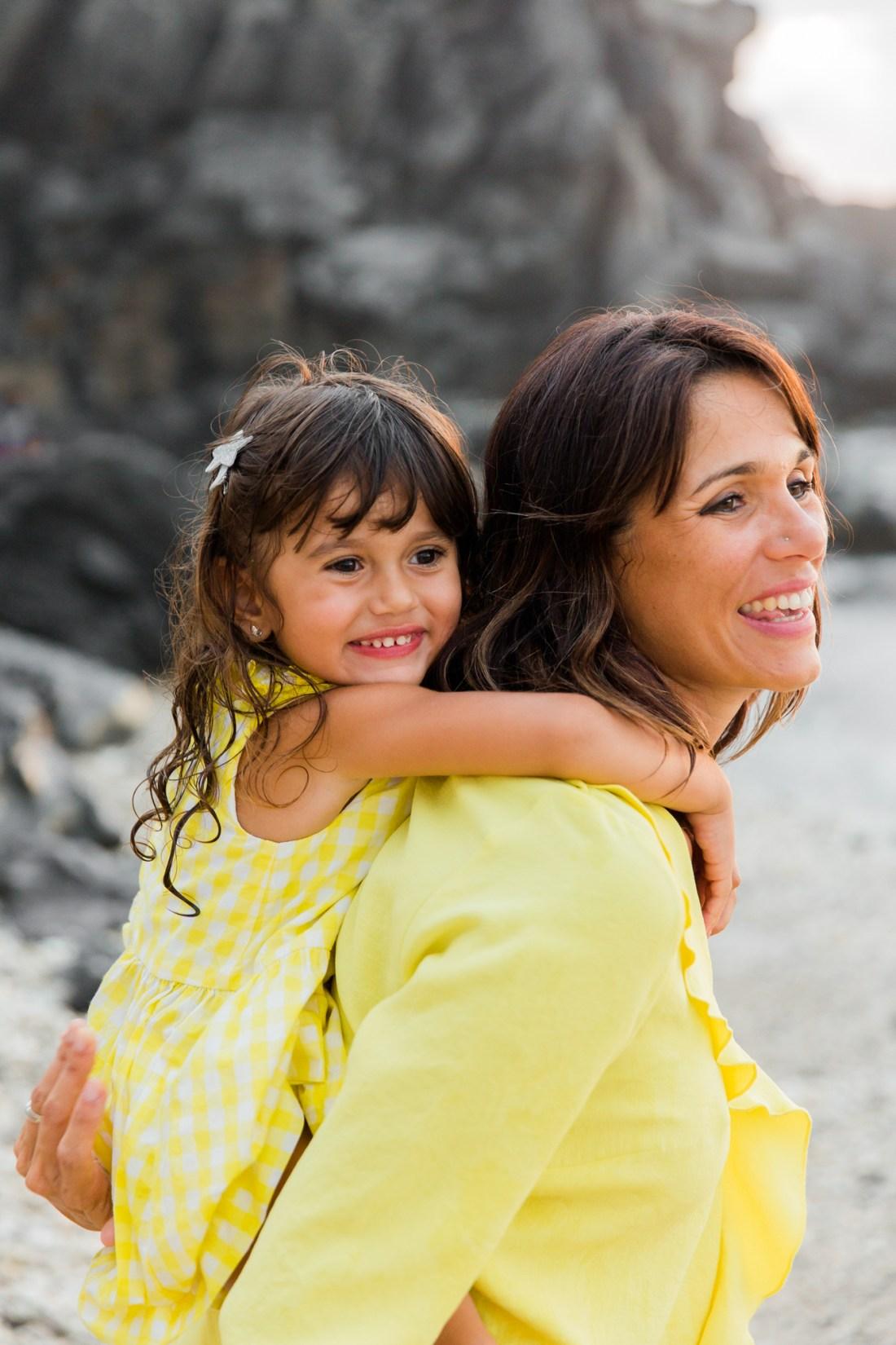 Une enfant sur le dos de sa maman à la plage