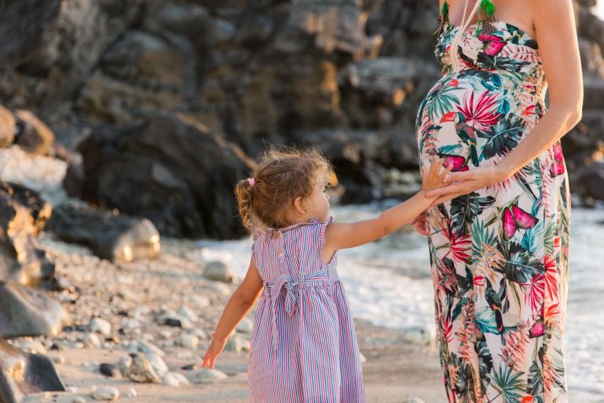 Une petite fille qui touche le ventre de sa maman enceinte lors d'une séance photo grossesse