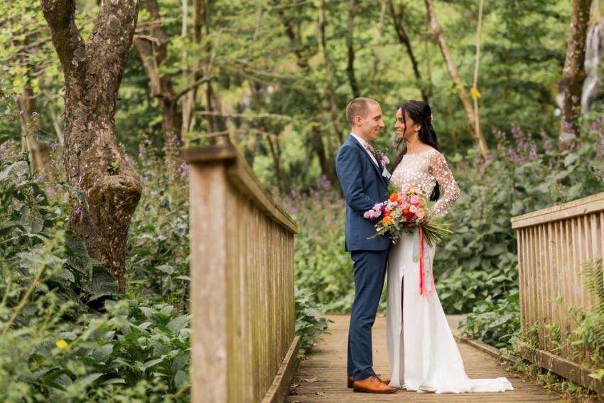 Des mariés à l'anse des cascades de Sainte-Rose avec un bouquet de fleurs tropicales