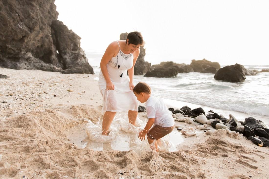 Une maman et son enfant qui s'amuse à sauter dans l'eau sur une plage de la Réunion lors d'une séance famille