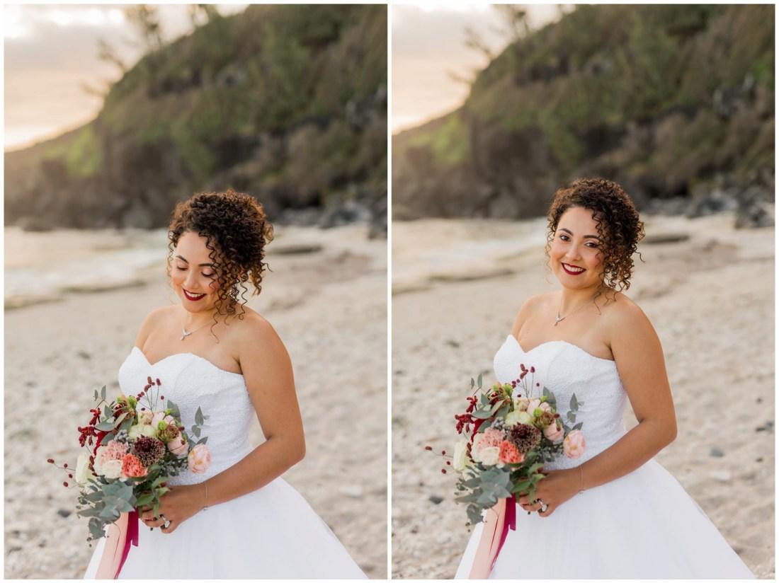 Une splendide mariée sur la plage de grande anse avec un bouquet de fleur dans les tons de rouge marsala et rose poudré