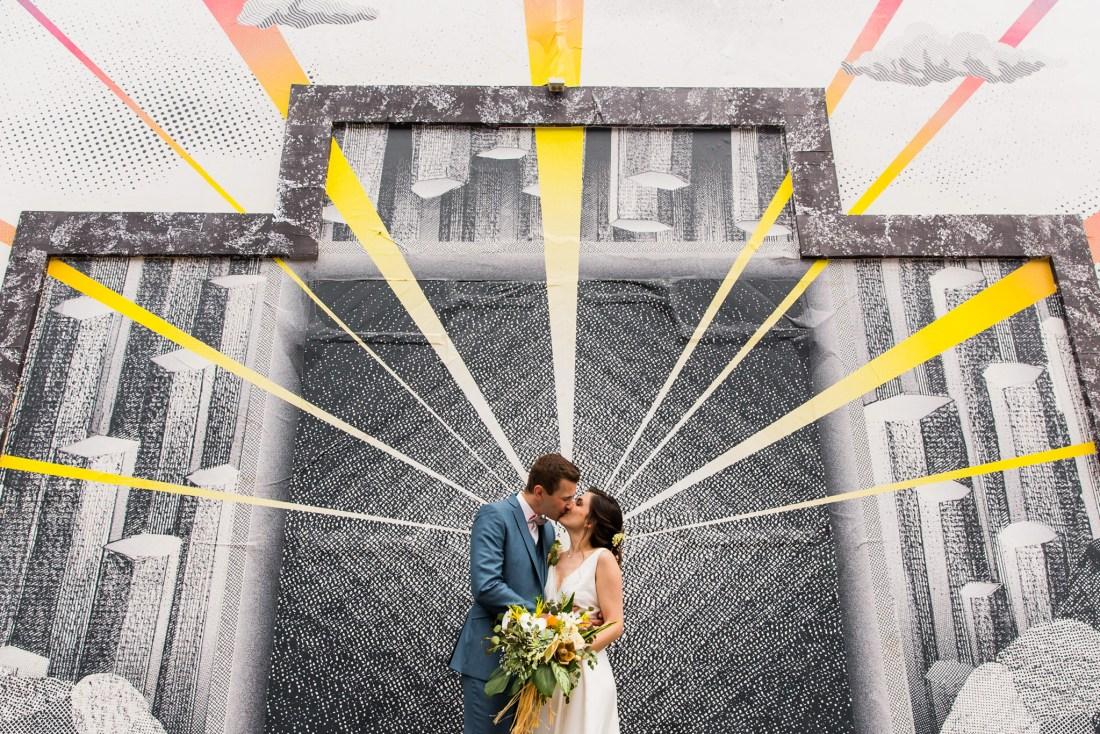 Un couple mariés qui s'embrassent devant une oeuvre d'art rayonnante de Saint Paul