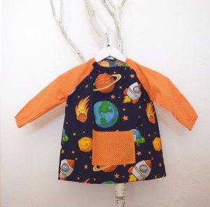 Bata para guardería con estampado de planetas y cohetes en azul marino y lunares naranja.