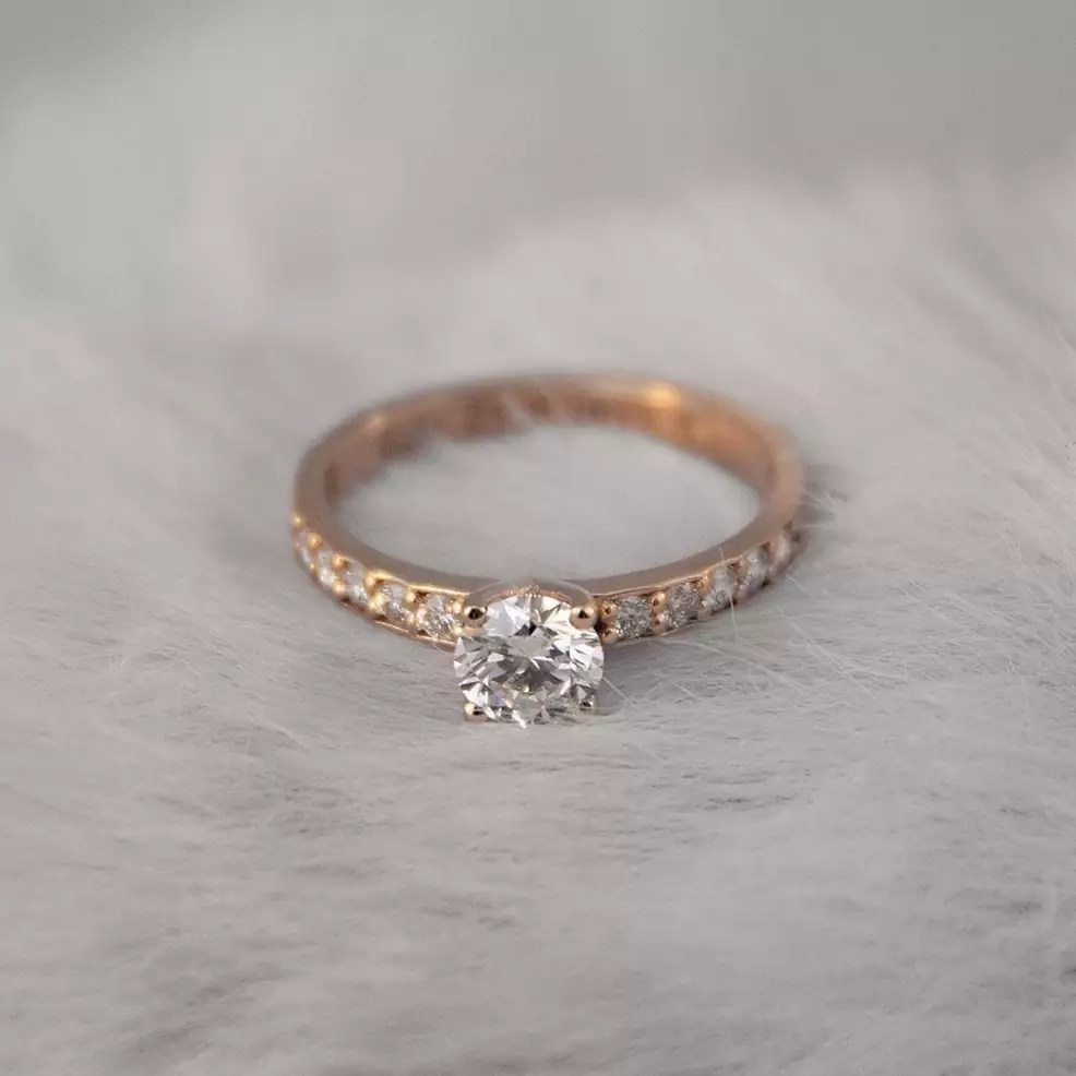 A gold diamond ring lying on a white fur-like surface.