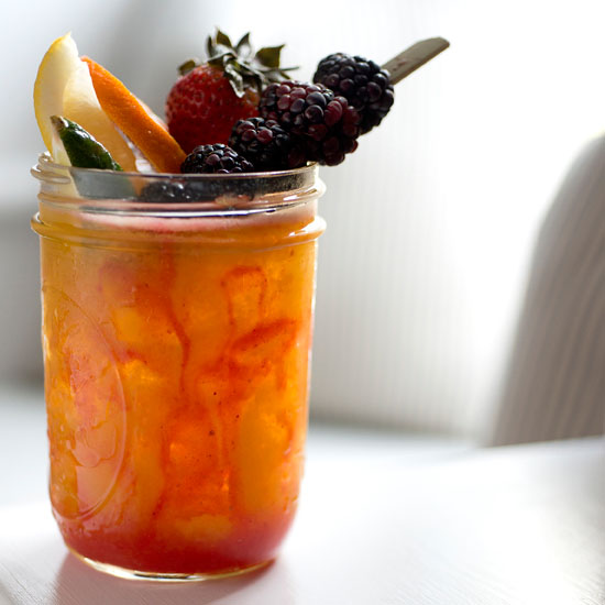 Orange cocktail with berries as a garnish