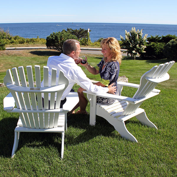 Couple sitting in coastal waterfront lawn