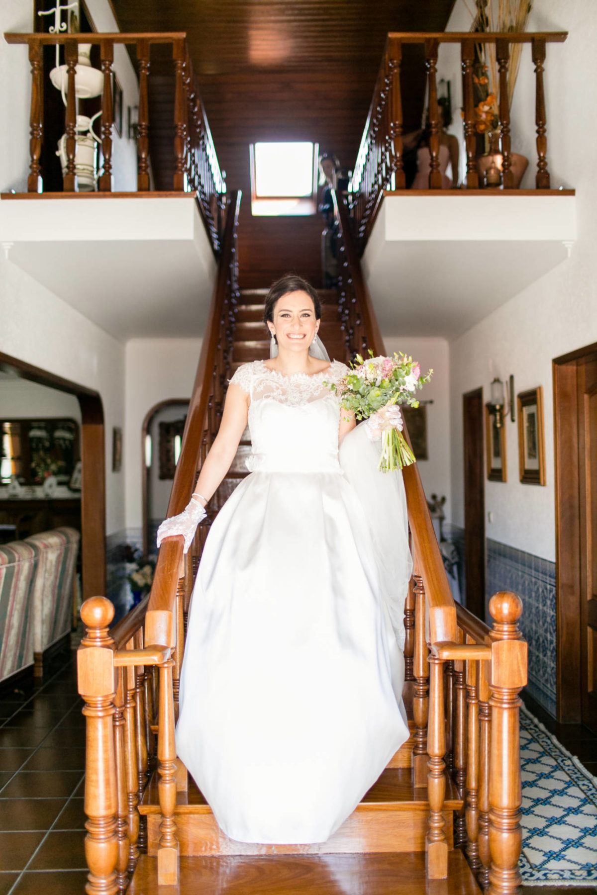 Bride coming down the stairs holding bouquet