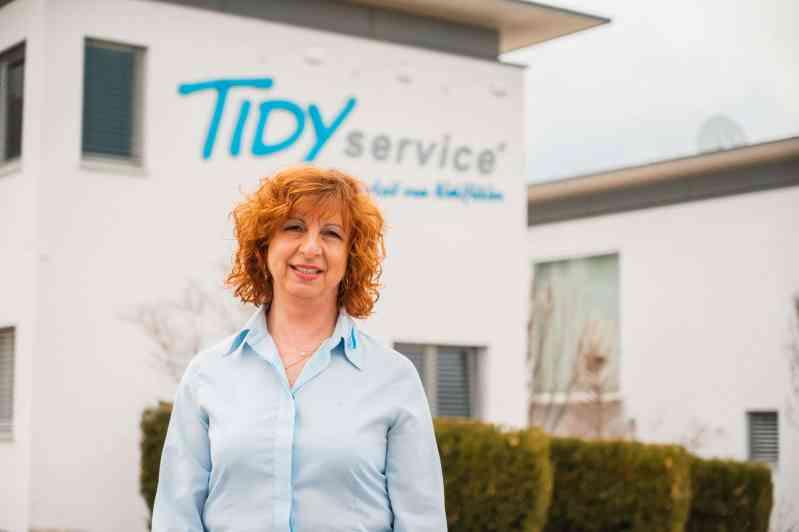 TIDYservice Mitarbeiterin vor dem Geschäftsgebäude