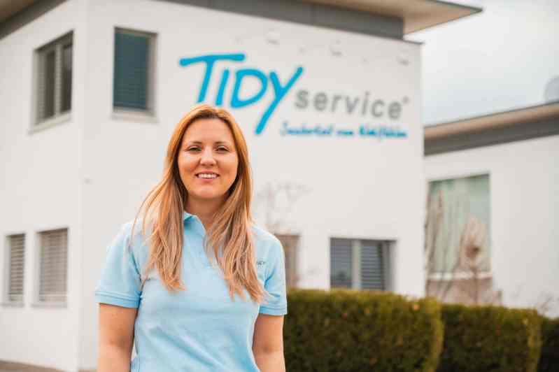 Mitarbeiterin vor der TIDYservice Geschäftsstelle