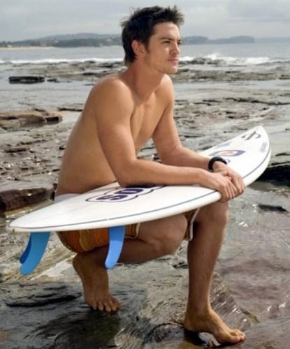 Craig Horner knealing surfboard beach