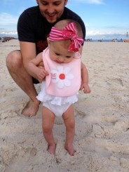 Putting her toes in the sand for the first time!