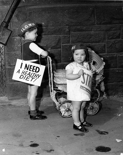 """Two young children picket for the ILGWU carrying placards including 'I Need a Healthy Diet!' outside the Kolodney and Myers Employment Office"" by the Kheel Center at Cornell University, used under CC-BY 2.0."